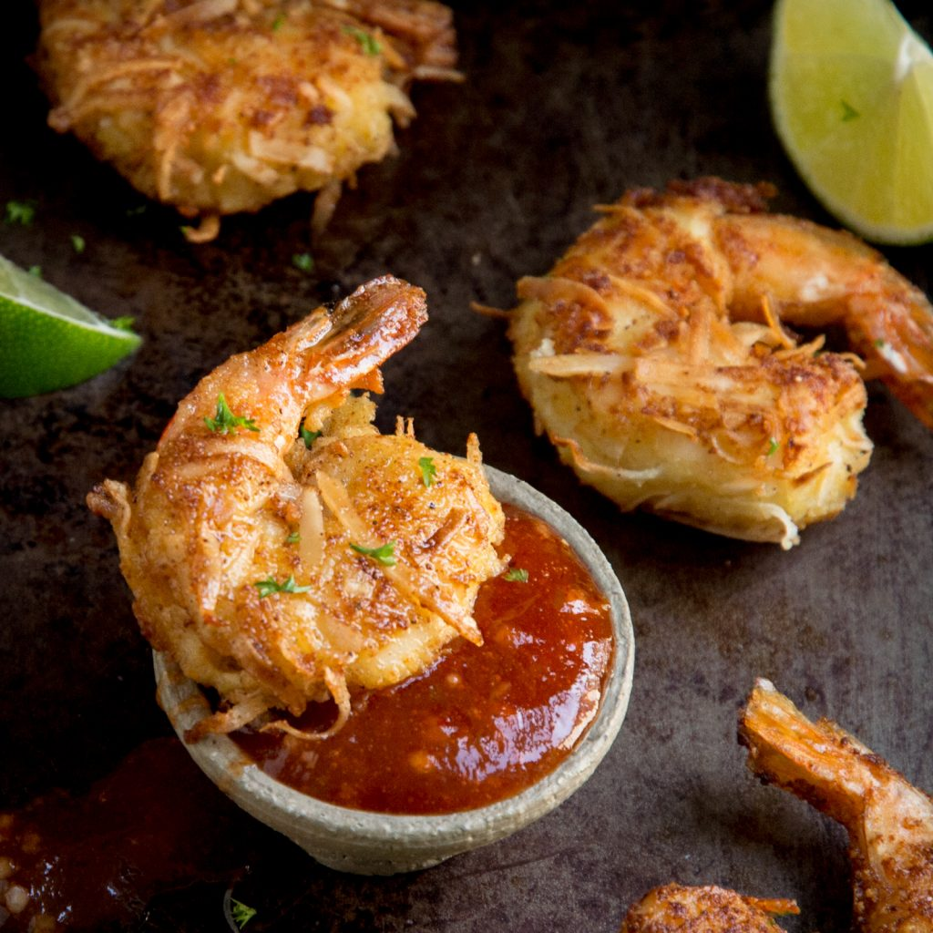 Close up photo of a cooked coconut shrimp dipped in its sauce.