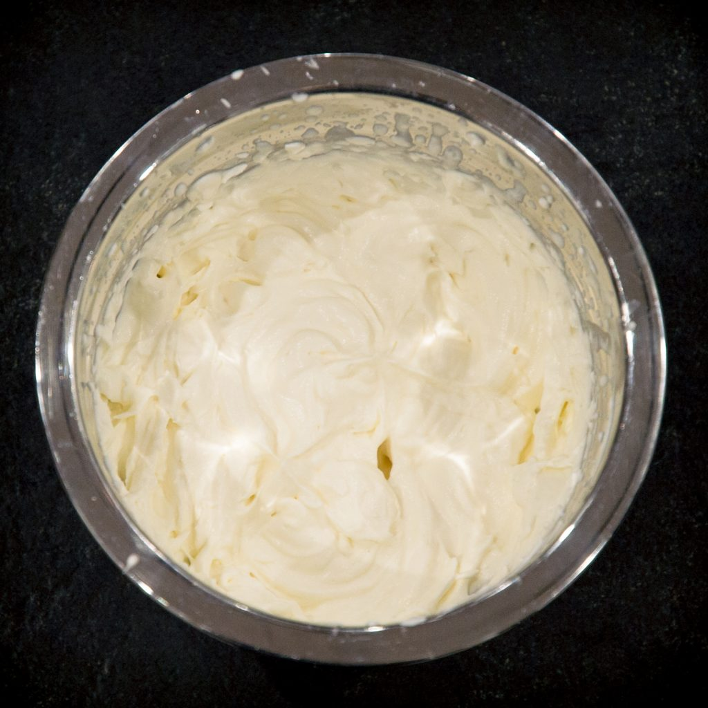 Process photo of whipped cream mixture with stiff peaks.