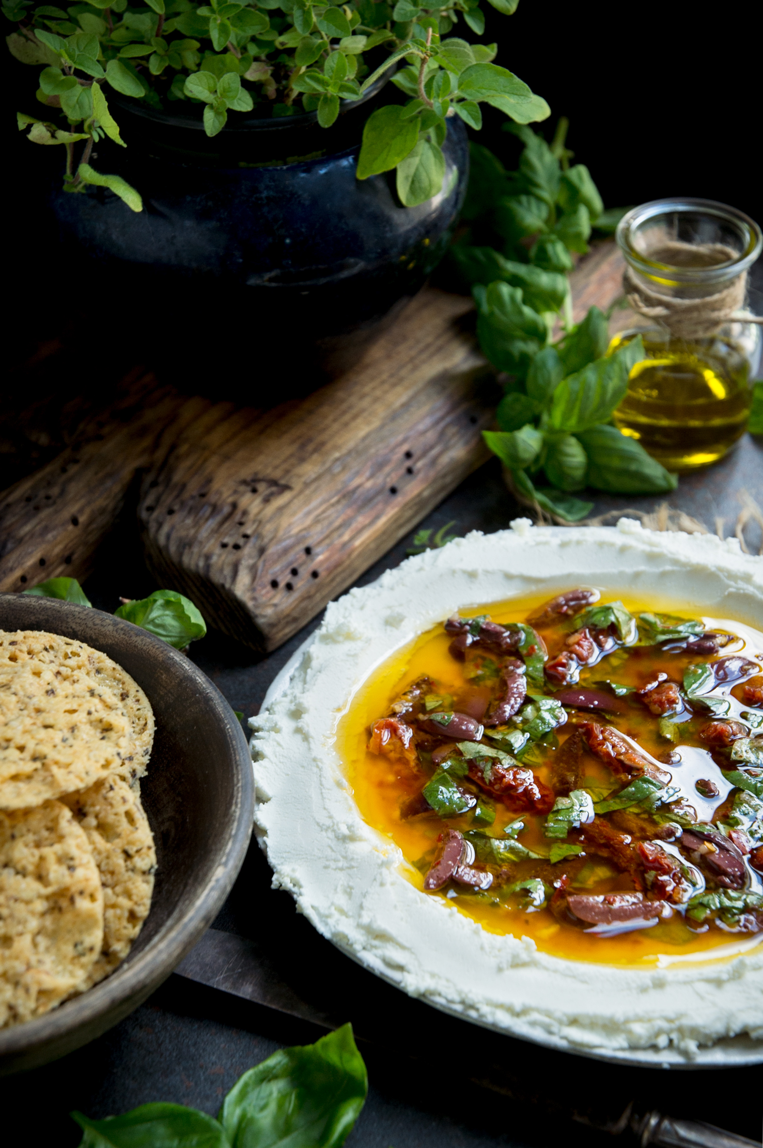 Vertical photo of herbed goat cheese spread with a bowl of crackers