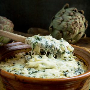 Spoonful of Keto Spinach Artichoke Casserole with stretchy cheese.
