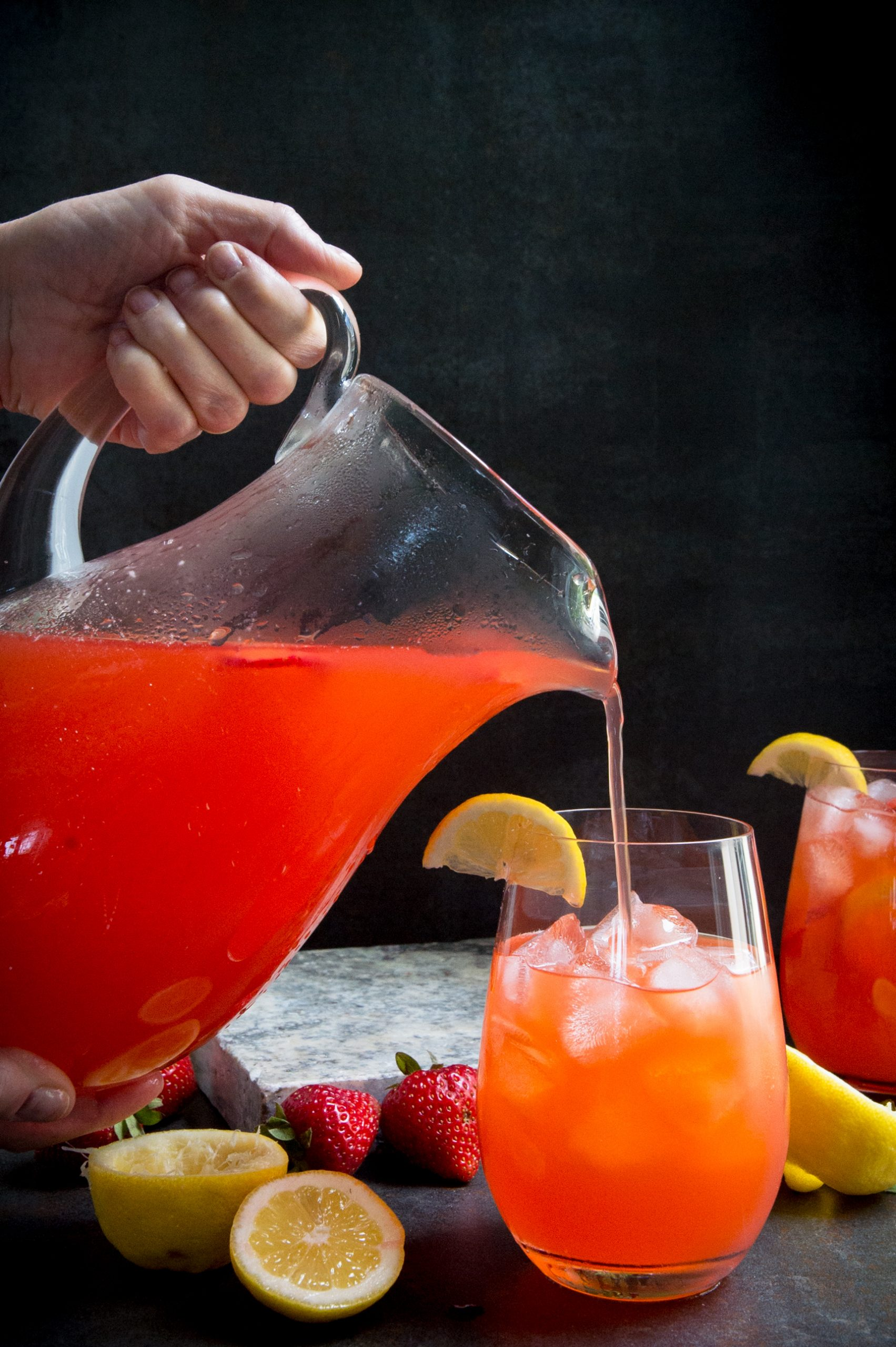 Pouring the sugar-free strawberry lemonade into a glass.