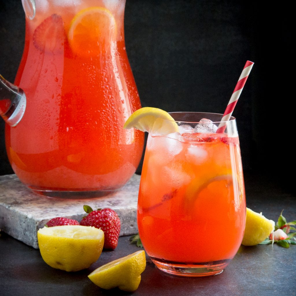 Glass of sugar free strawberry lemonade with pitcher behind it