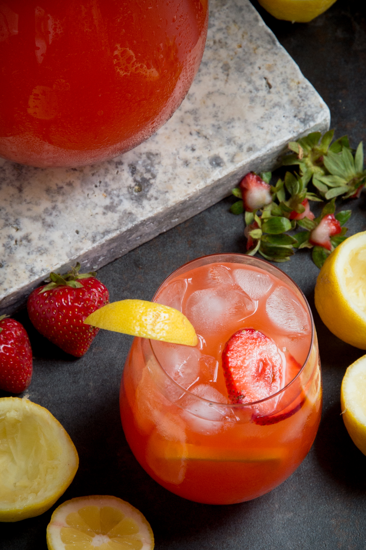 Overhead shot of Glass of sugar-free strawberry lemonade in front of pitcher