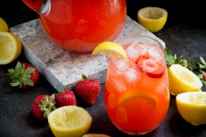 Glass of sugar-free strawberry lemonade in front of pitcher