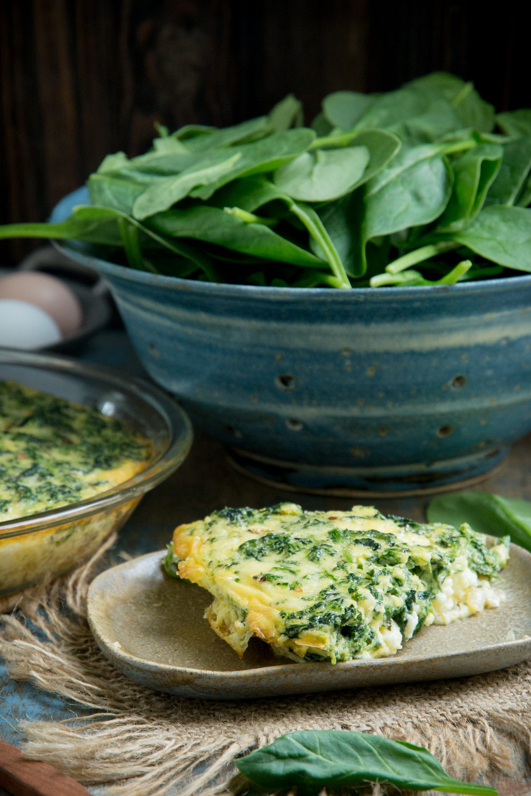 A slice of crustless spinach quiche in front of a bowl of spinach