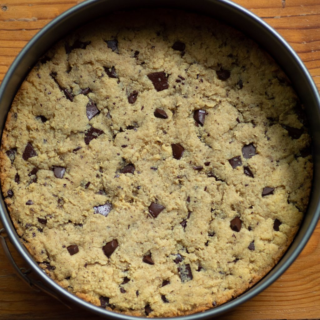 Process photo of baked cookie cake with slightly golden edges.