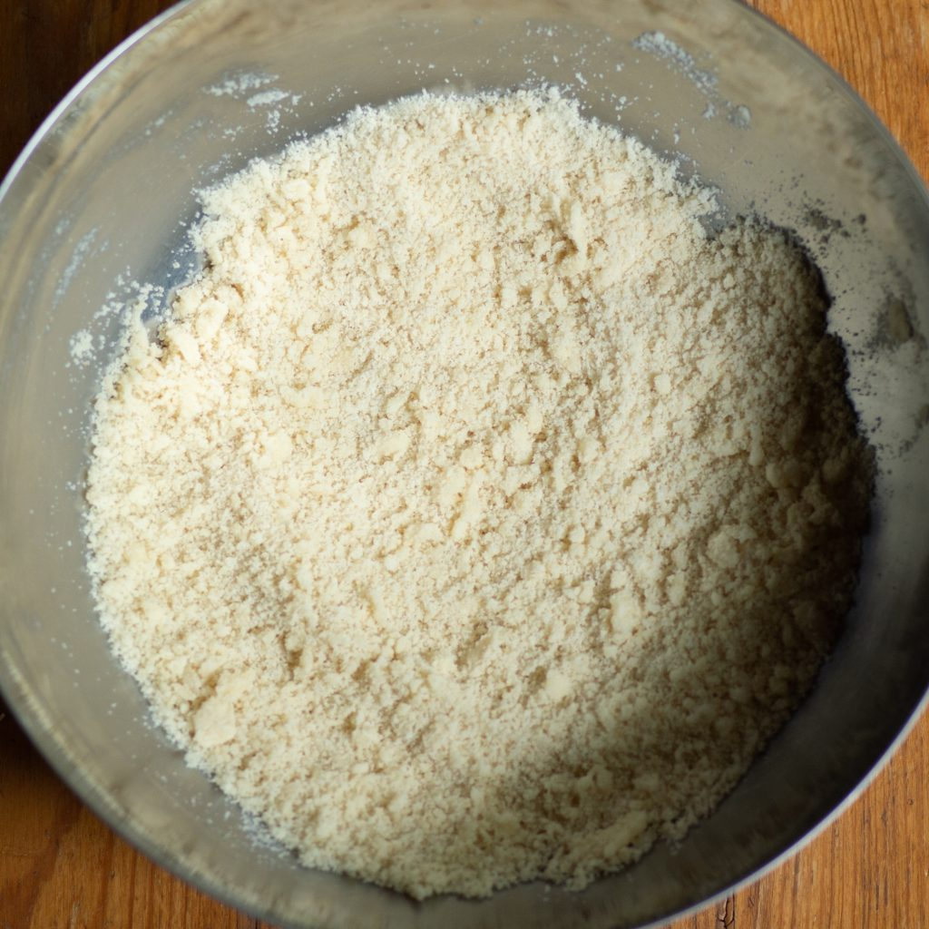 Process photo of cut butter added into dry ingredients forming a coarse crumb texture.