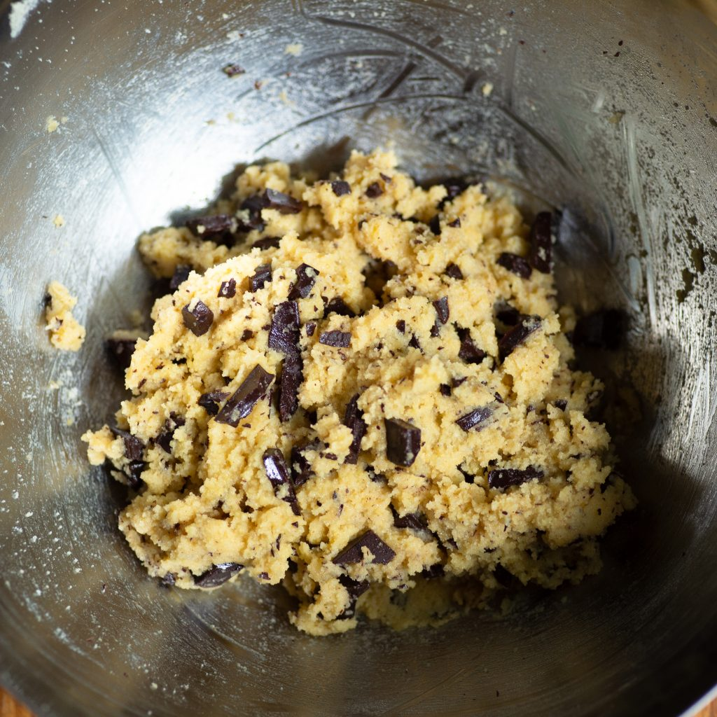Process photo of chocolate chips added into the ball-shaped cookie dough.