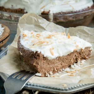 A piece of Coconut Chocolate Pie topped with whipped cream and toasted coconut.