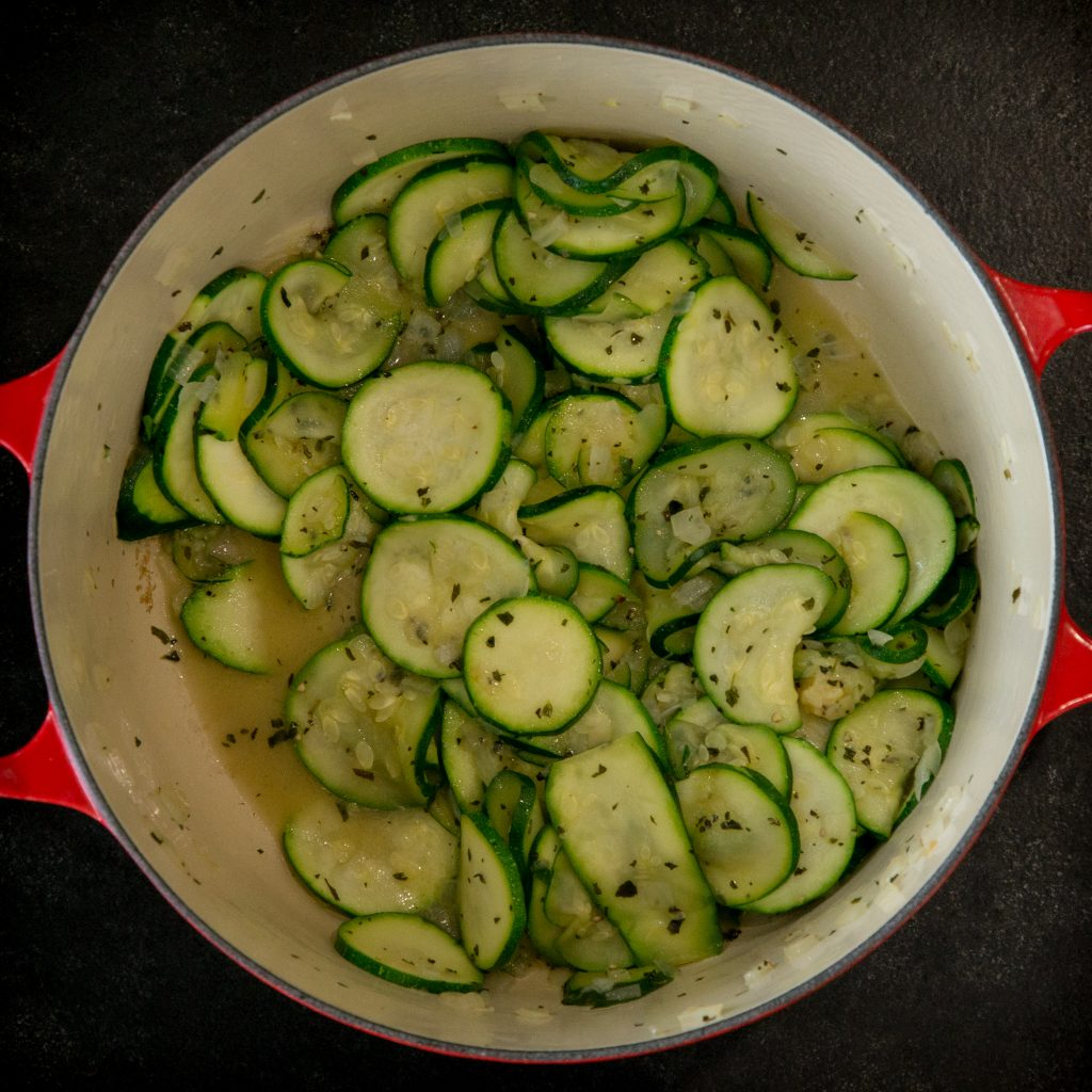 Adding zucchini to the soup pot.