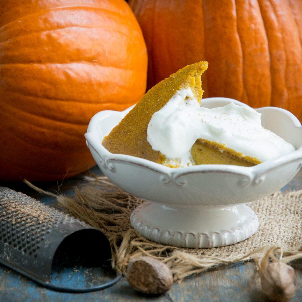 Keto Pumpkin Custard in a bowl with whipped cream