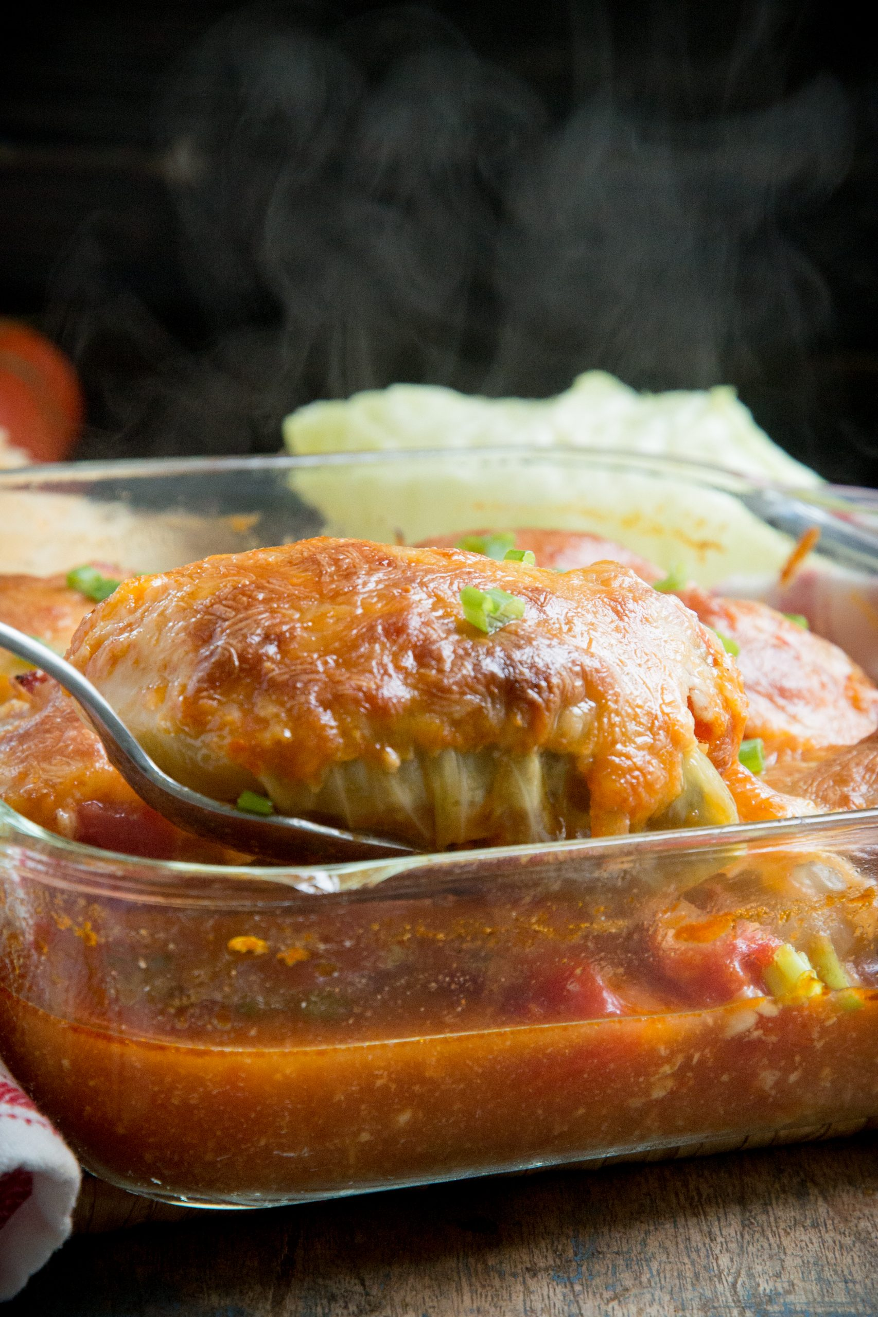 Lifting a cabbage roll from the baking dish.