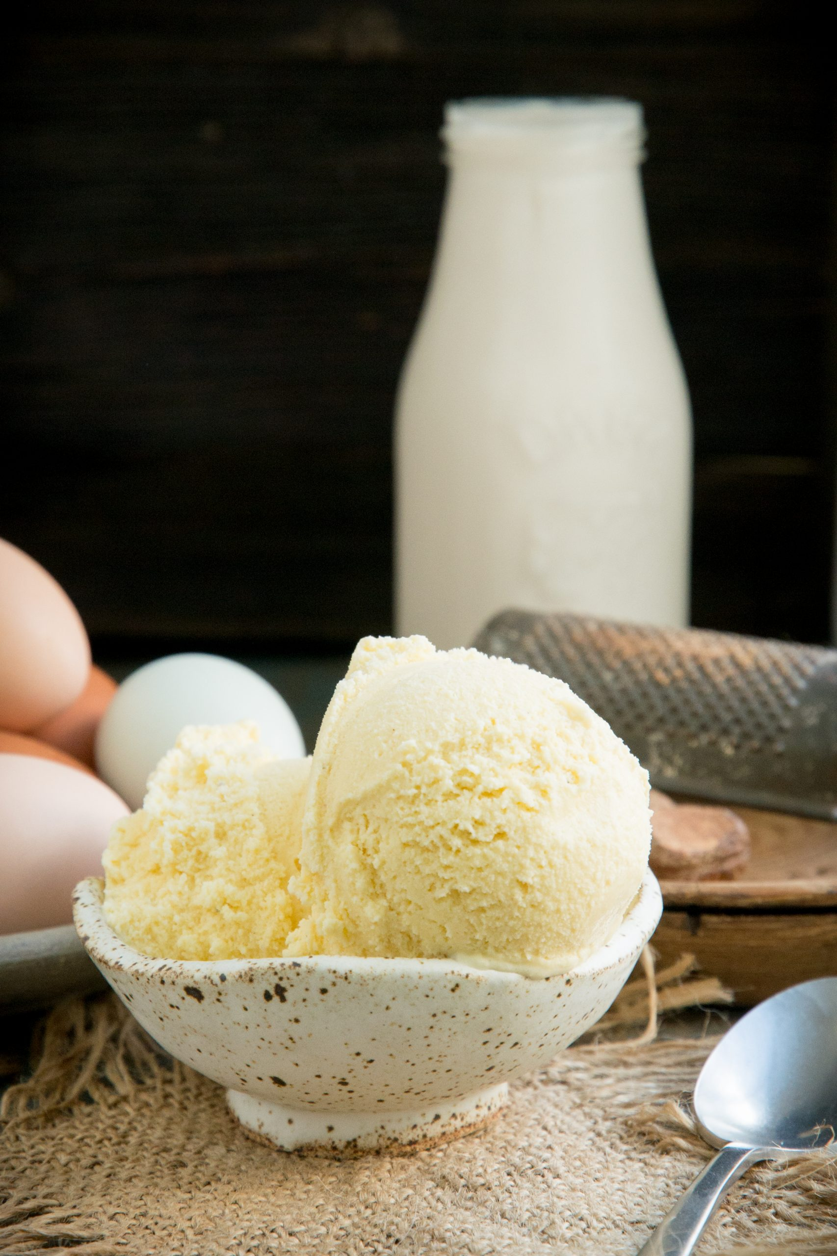 Ice cream with cream and eggs in the background.
