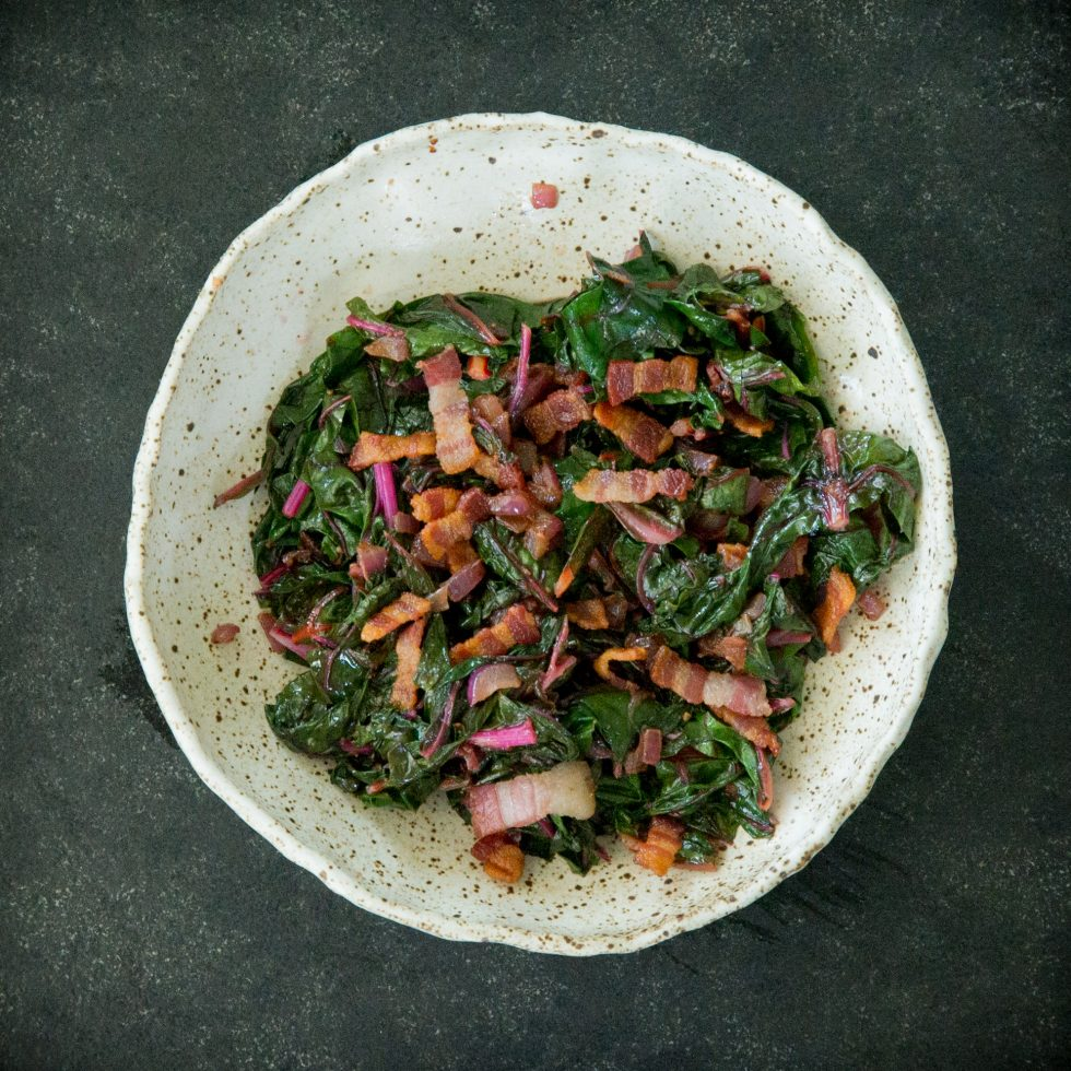 Adding the bacon to the chard.