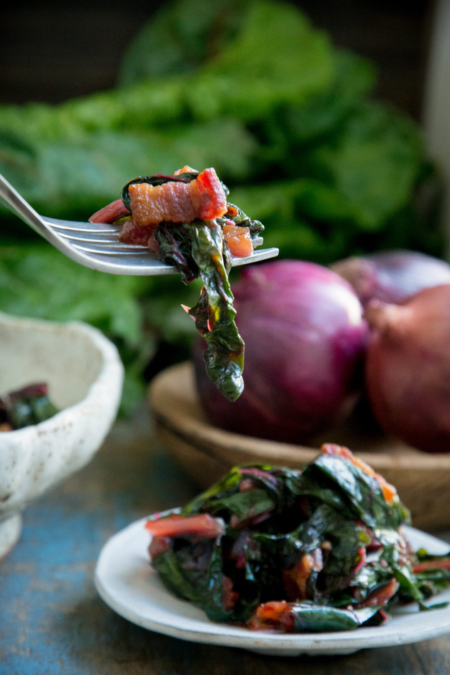 Wilted chard with bacon and garlic on a fork.