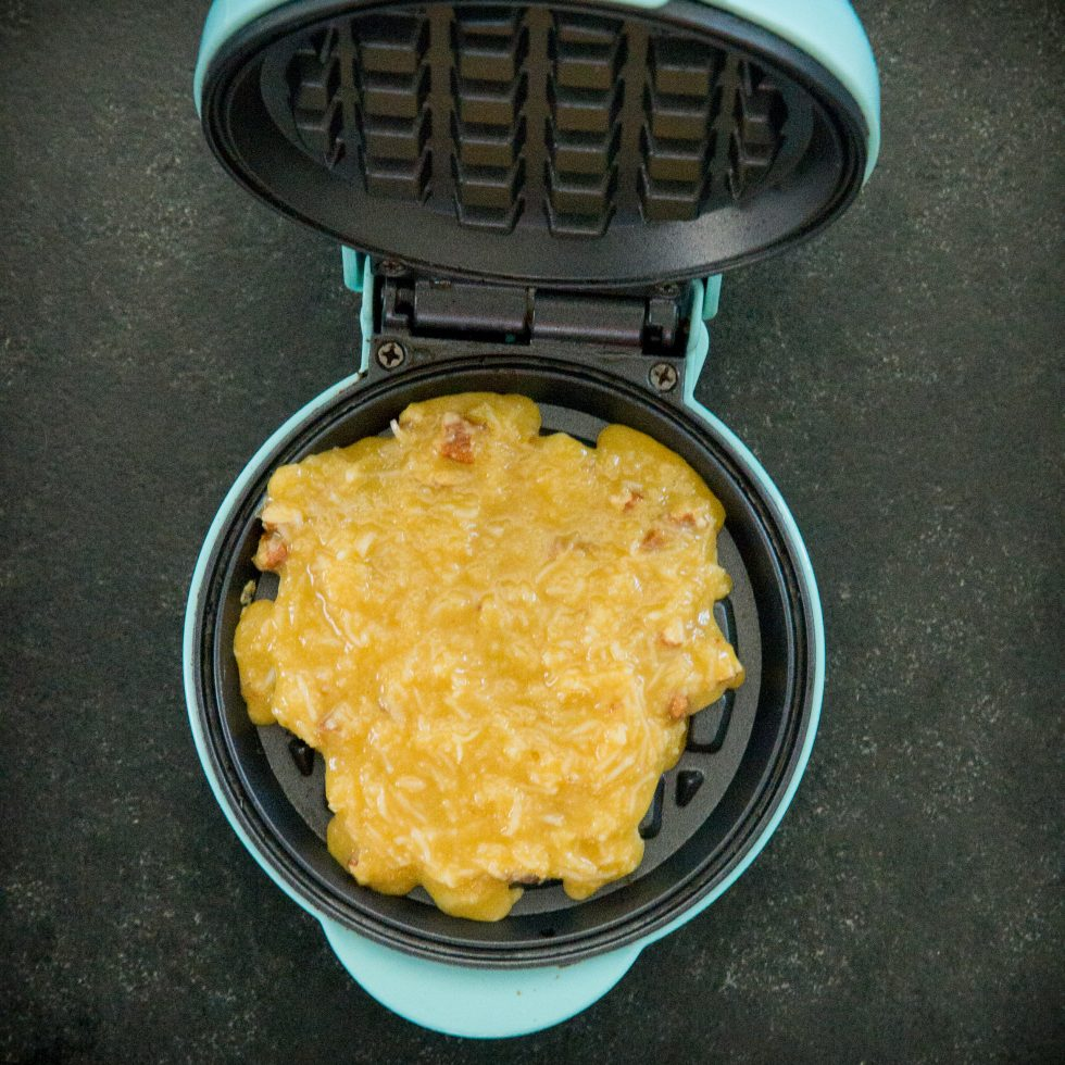 Putting the maple pecan chaffle batter in the waffle maker.