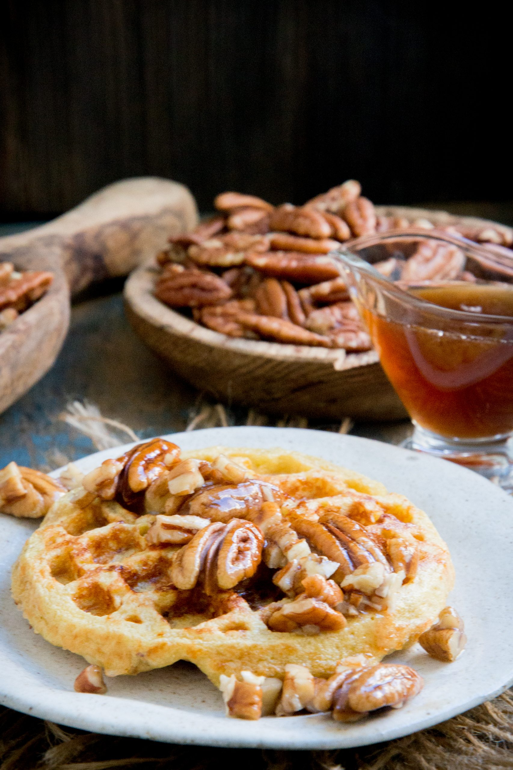 Maple pecan chaffles with pecans and syrup on top.