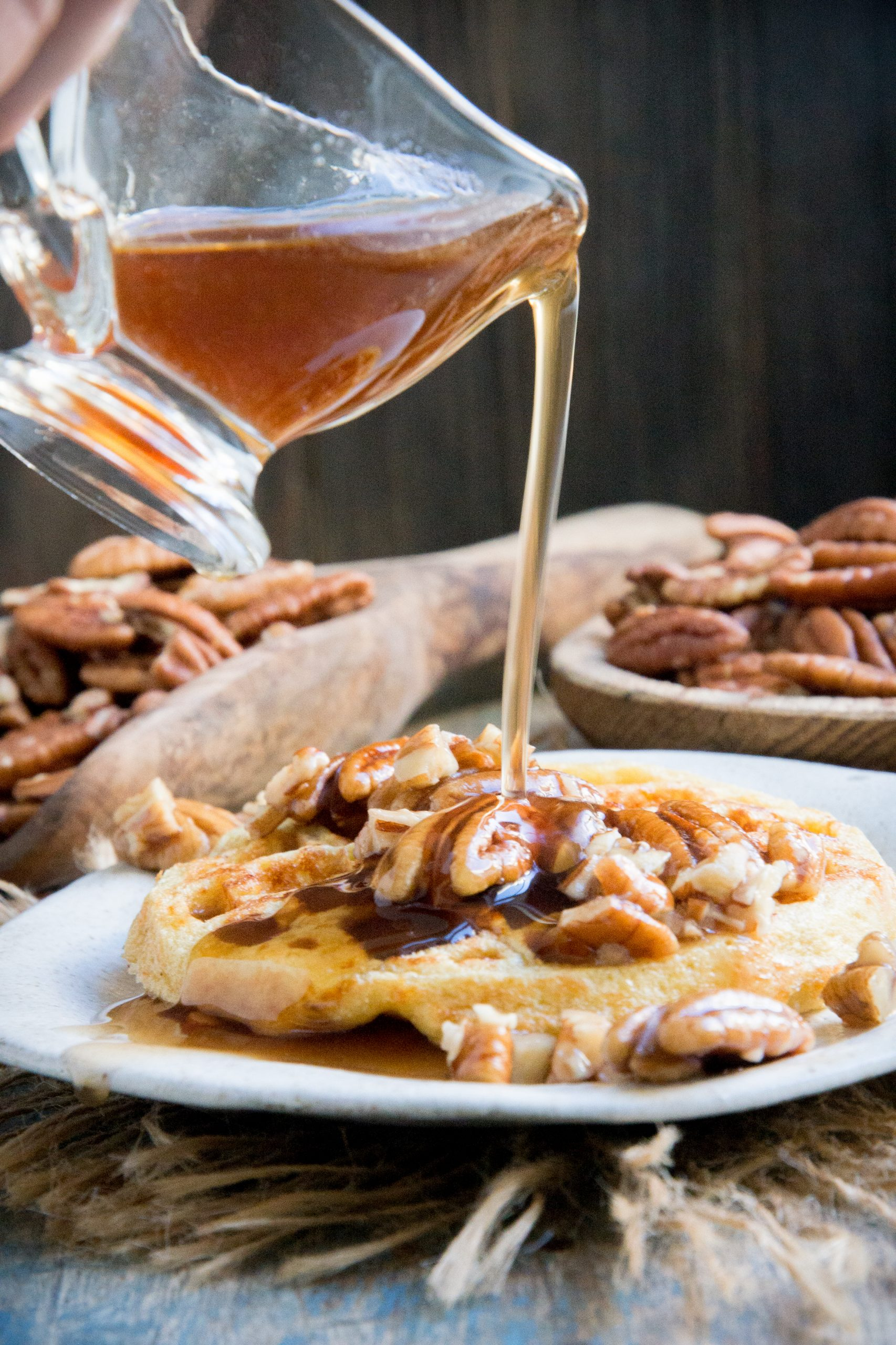 Pouring syrup on the keto maple pecan waffle.