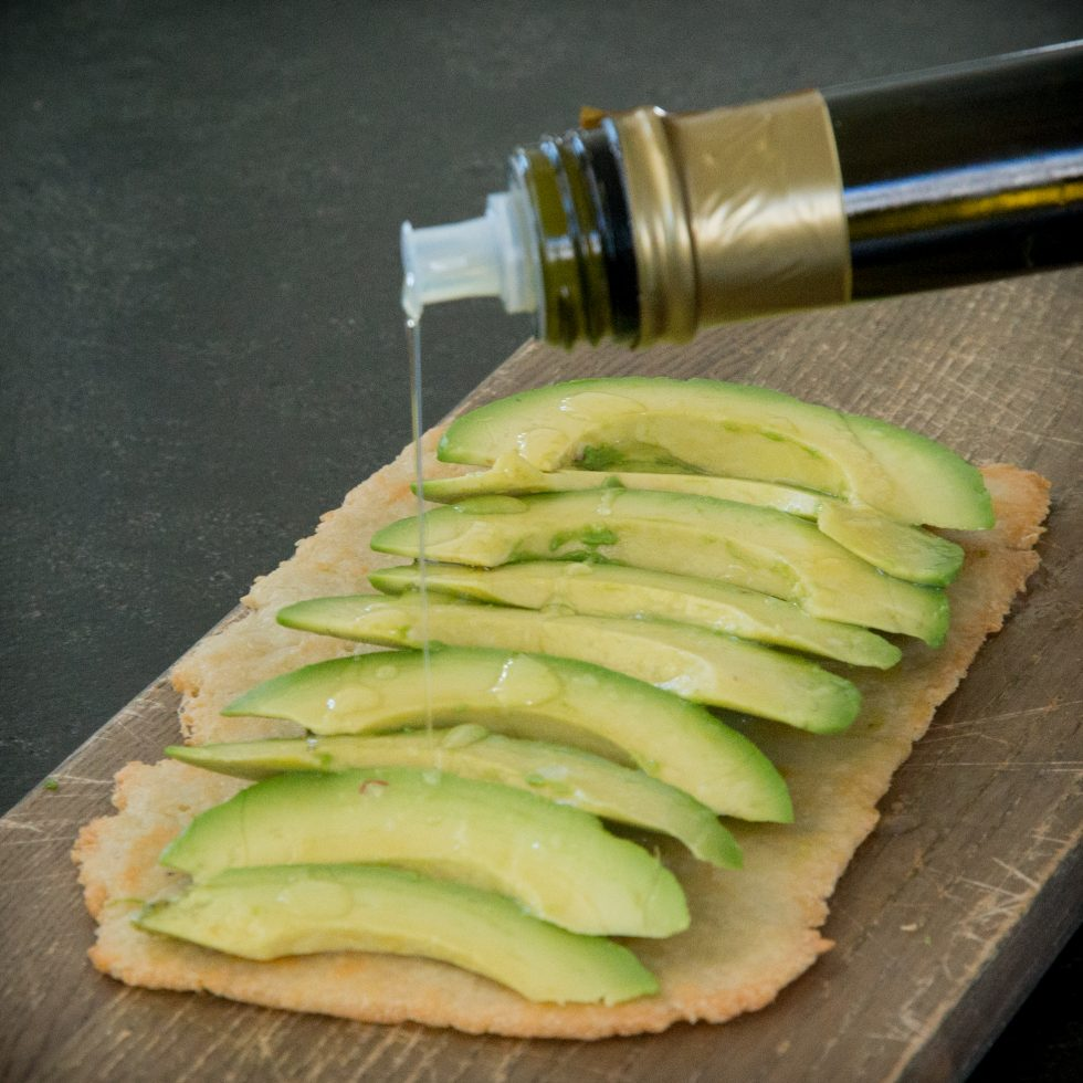 Pouring olive oil over the avocado.