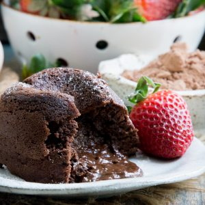 Chocolate lava cake opened and spilling onto a plate.