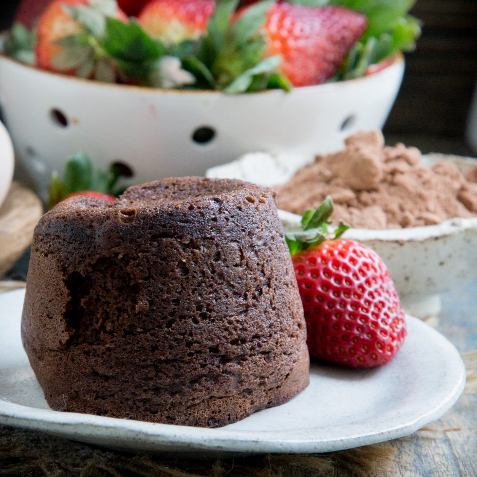 Chocolate lava cake with a strawberry on a plate.