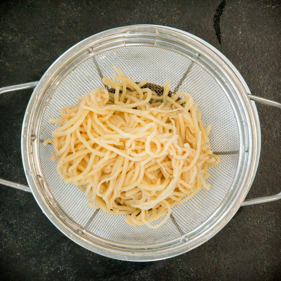 Draining the palm pasta.