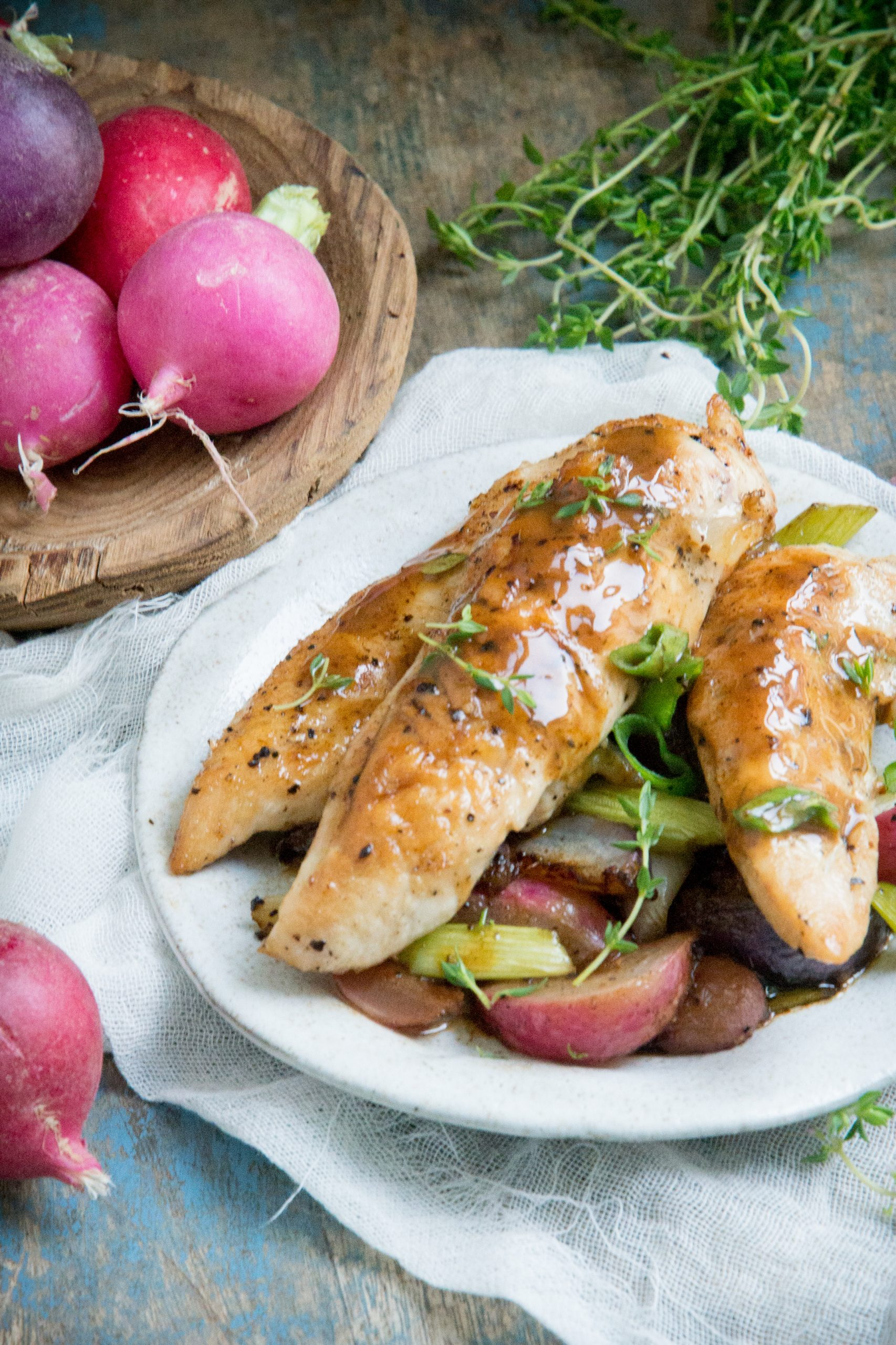 Chicken tenders, roasted radishes and onions on a plate.