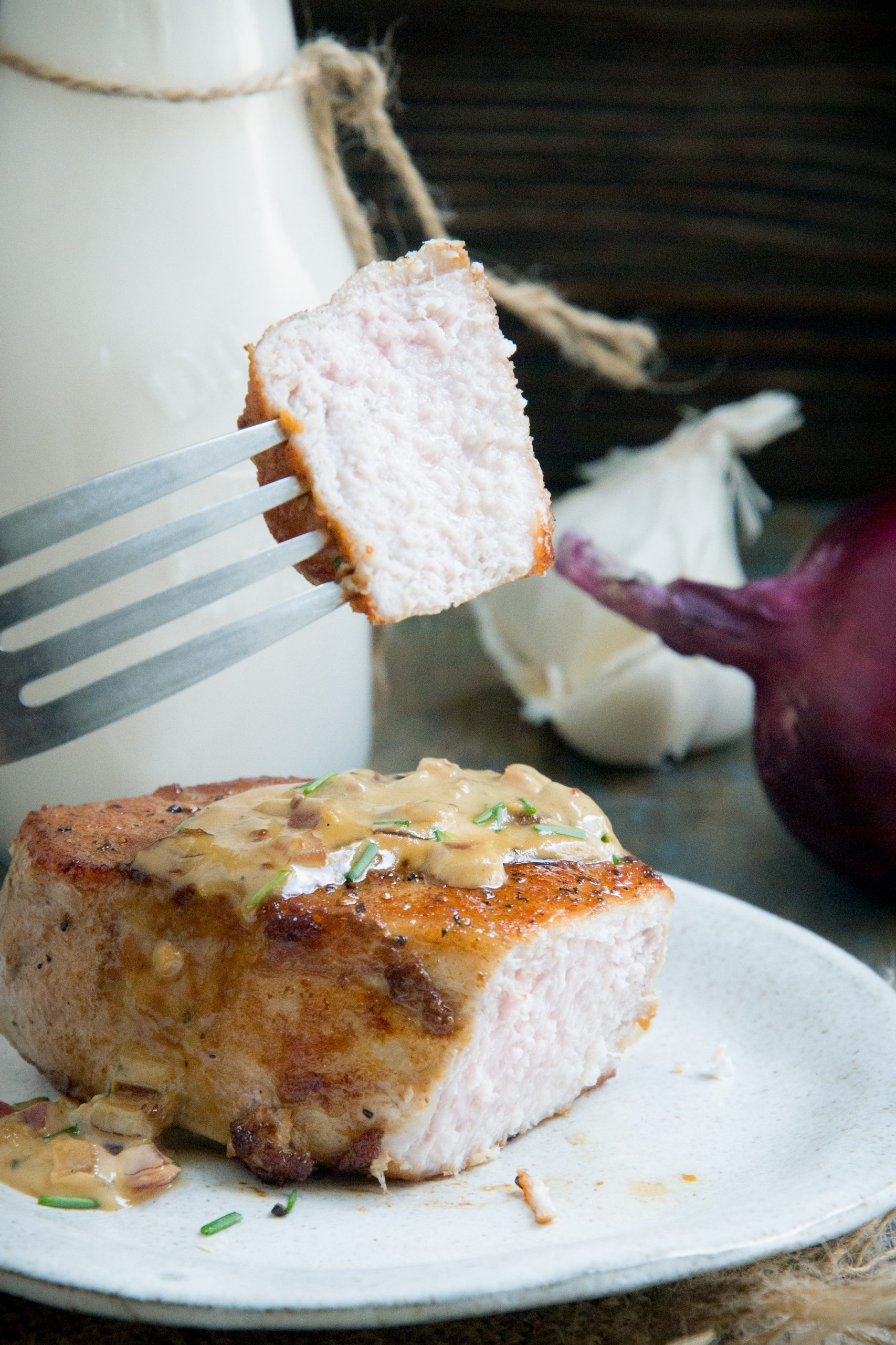 Taking a bite of the pork chop with garlic chive cream sauce.
